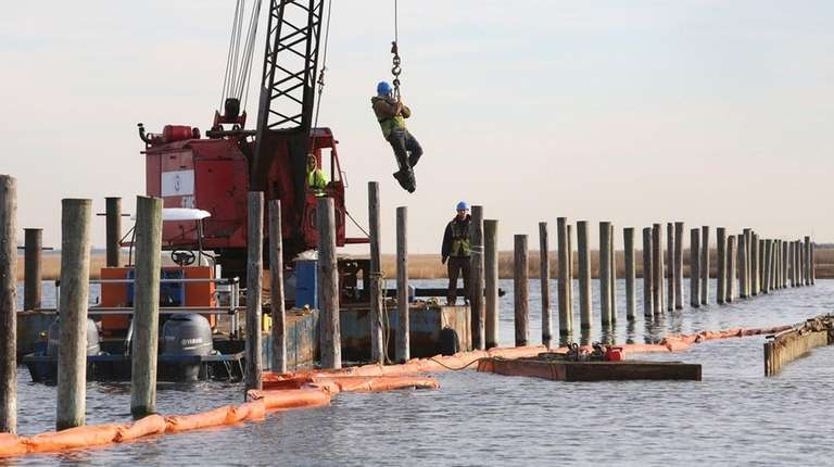 A contractor is hoisted to a small dock