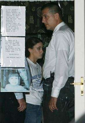 Casey Anthony,(left) in handcuffs stands in her home
