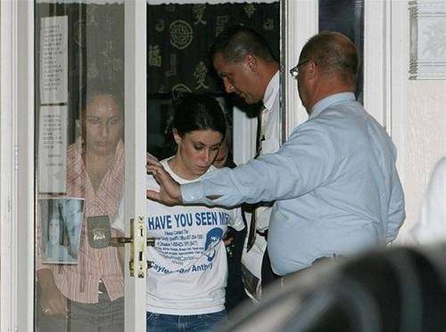 Casey Anthony,(center) in handcuffs walks out her home
