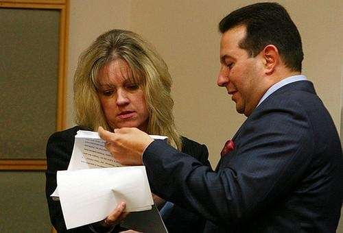 Casey Anthony's attorney Jose Baez (right) hands over