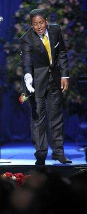 Singer Jermaine Jackson throws a rose on Michael