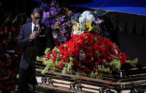 Singer Usher performs next to the casket at
