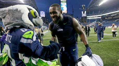 Seattle Seahawks safety Kam Chancellor greets Blitz, the
