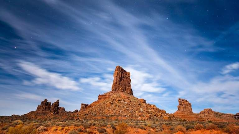 Moonlight illuminates sandstone buttes in the Valley of