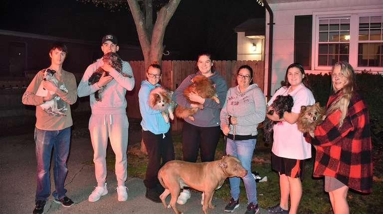 Family and neighbors hold the seven dogs that