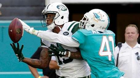 Dolphins cornerback Byron Maxwell attempts to block a