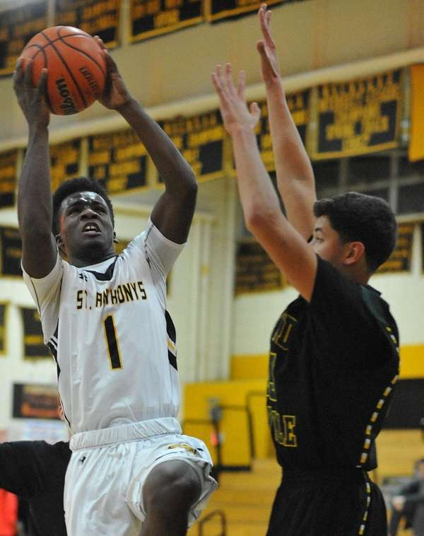 St. Anthony's Jon Harewood, left, drives to the