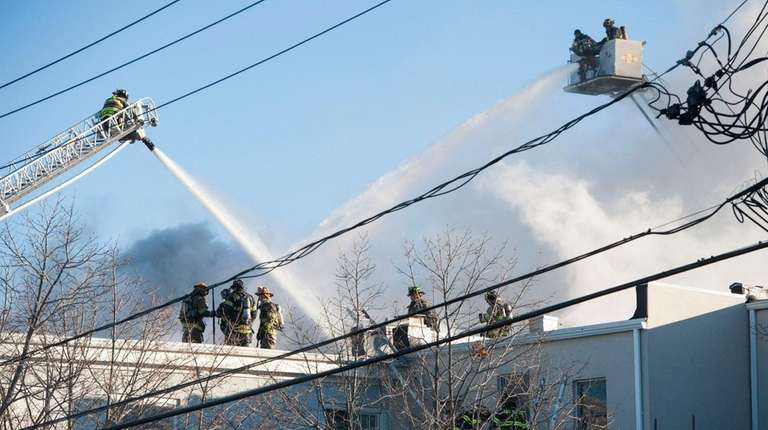 Firefighters battle a multiple structure fire on Main