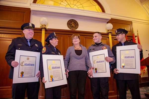 Mary Feeney, center, stands with Nassau Police officers