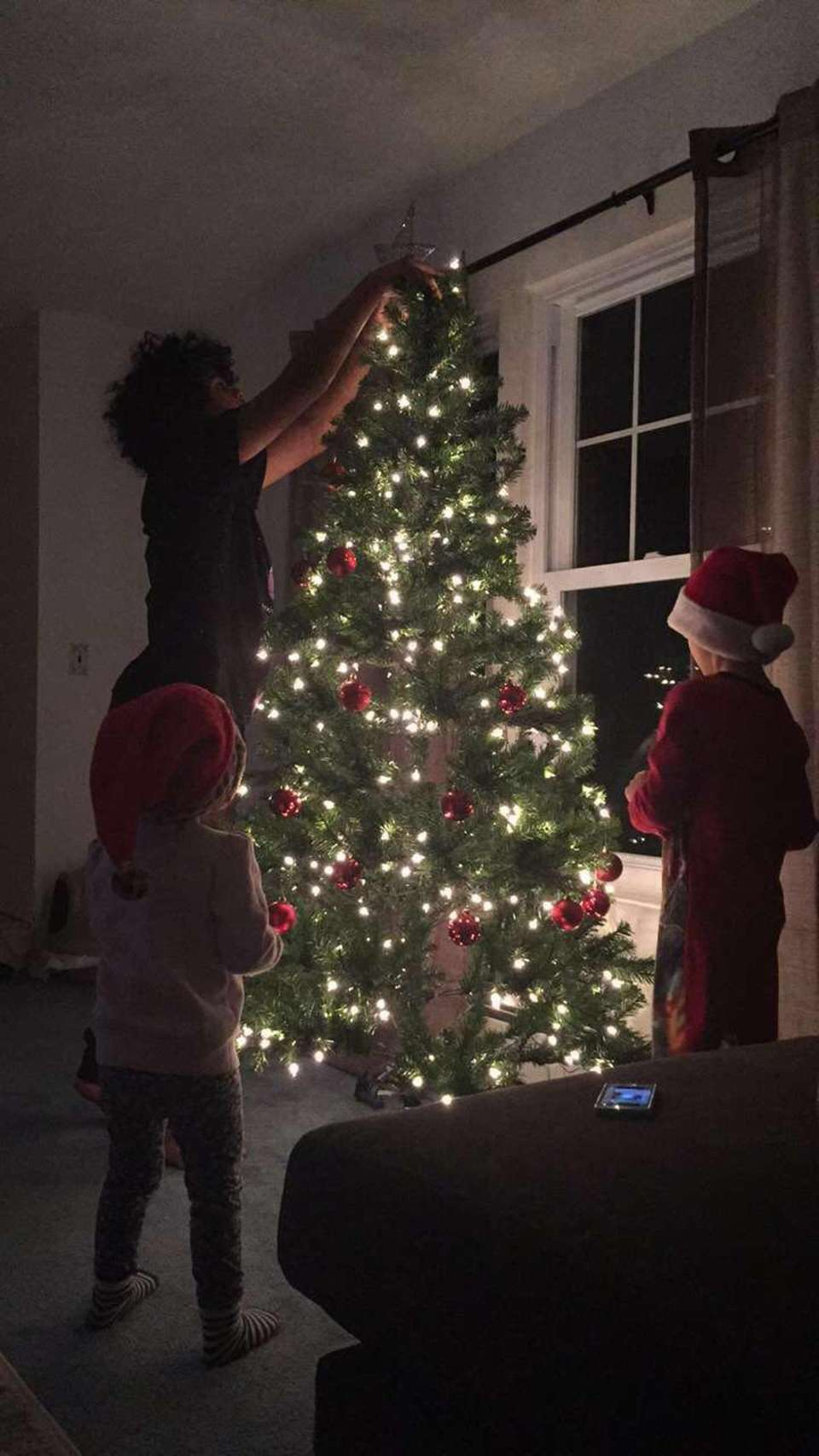 Decorating the tree, Khalil putting up the star