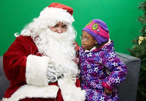 Sanaa Colin, 9, of Brentwood sits with Santa