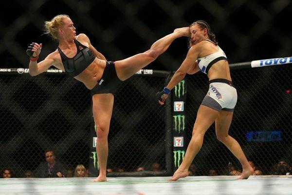 UFC bantamweight champion Holly Holm, left, kicks Miesha