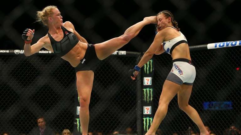 UFC bantamweight champion Holly Holm, left, kicks Miesha