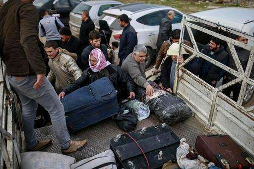 Syrians put their belongings into vehicles after crossing