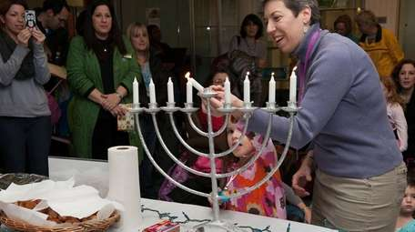 Rabbi Lina Zerbarini lights the menorah at the