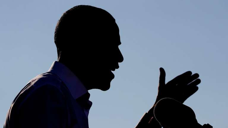 President Barack Obama is silhouetted as he speaks