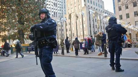 NYPD officers patrol near the Christmas tree at