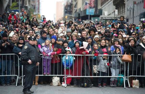 Crowds line the sidewalk and street during the
