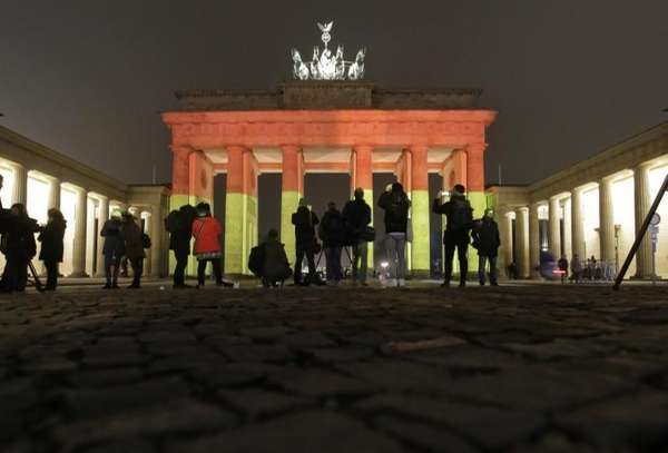 The Brandenburg Gate is illuminated in the colors