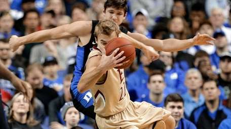 Elon's Steven Santa Ana is tripped by Duke's