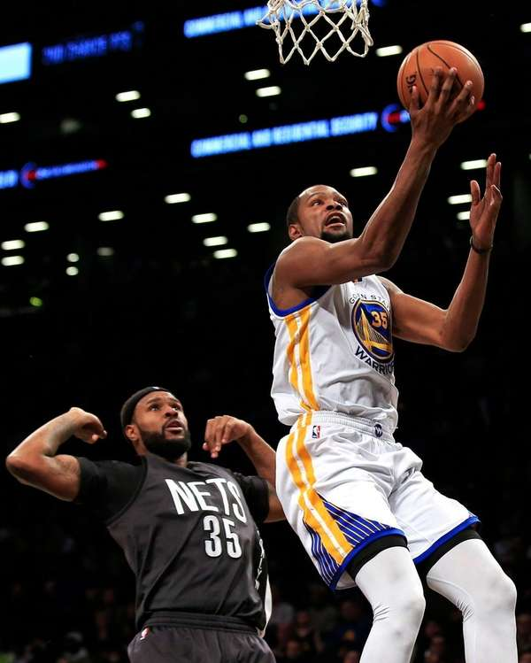 Warriors' Kevin Durant drives past Nets' Trevor Booker