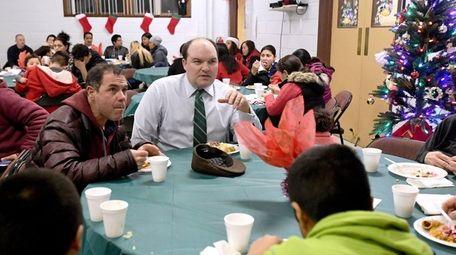 Greenport Village trustee Doug Roberts, center, attends a