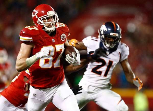 Kansas City Chiefs' player Travis Kelce (L) runs