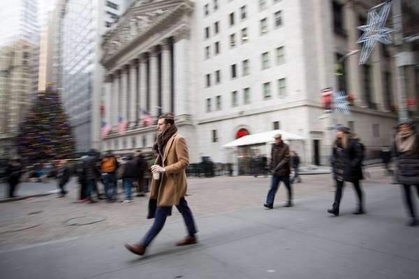Pedestrians walk along Wall Street in front of