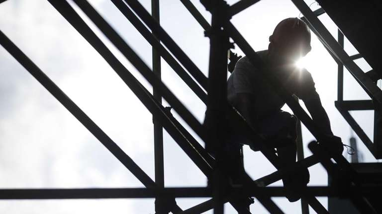 A construction worker sets up scaffolding.