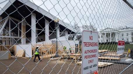 Workmen continue construction on the presidential reviewing stand