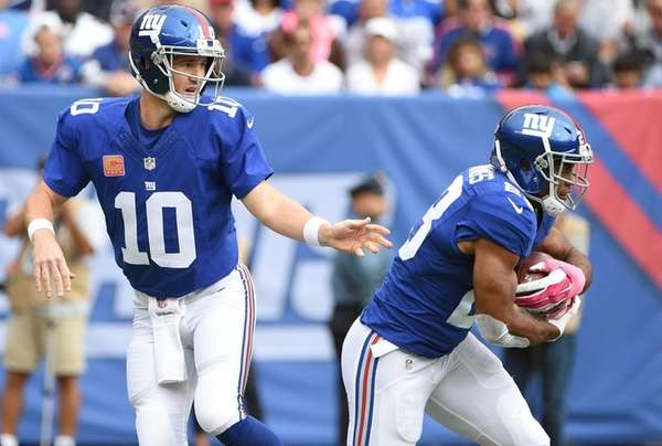 Eli Manning hands off to back Rashad Jennings