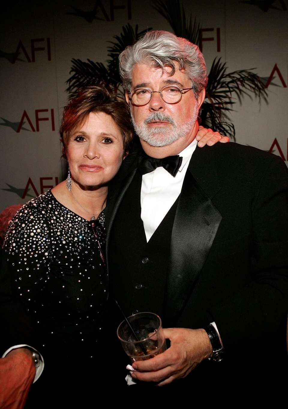 Actress Carrie Fisher and director George Lucas pose