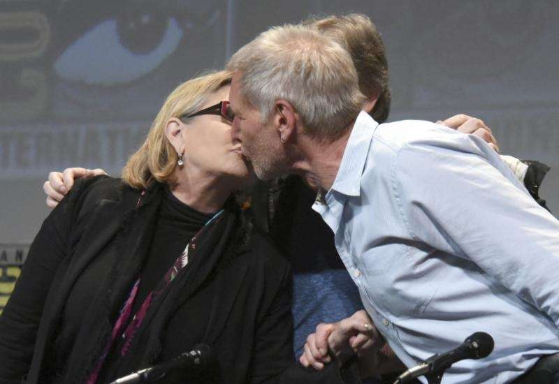 Carrie Fisher and Harrison Ford kiss at the