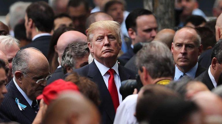 Republican presidential candidate Donald Trump (C) attends a