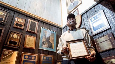 Eugene Burnett displays a plaque given to him