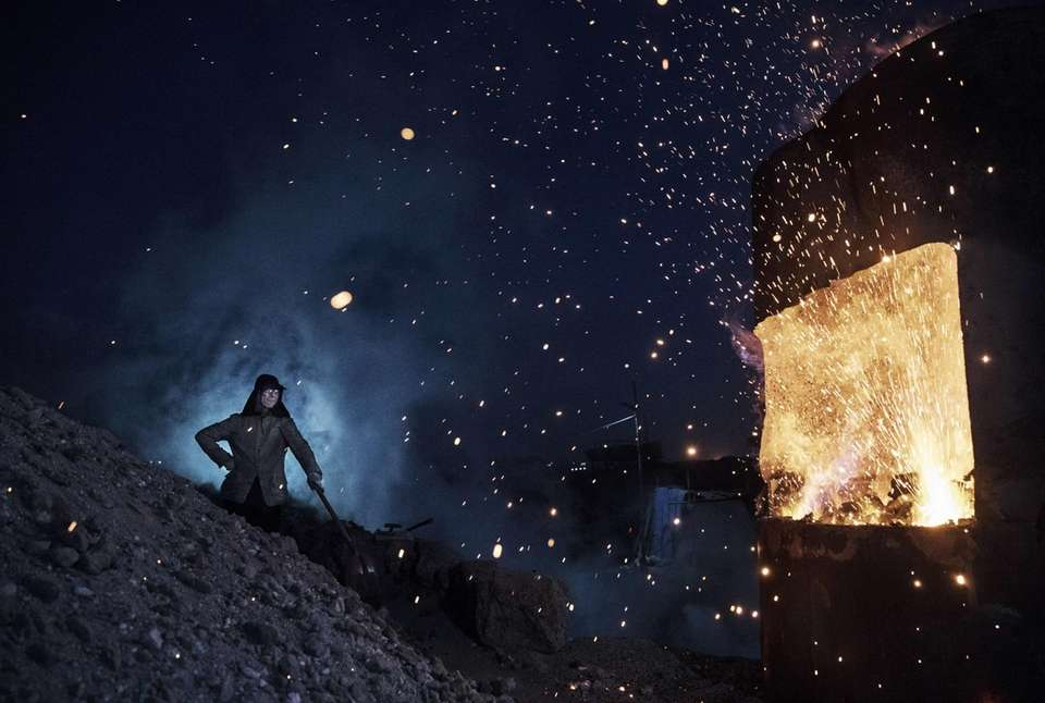 A Chinese laborer stands near a furnace as