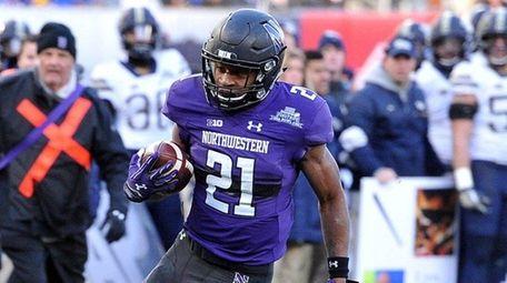 Northwestern running back Justin Jackson runsfor a 16-yard