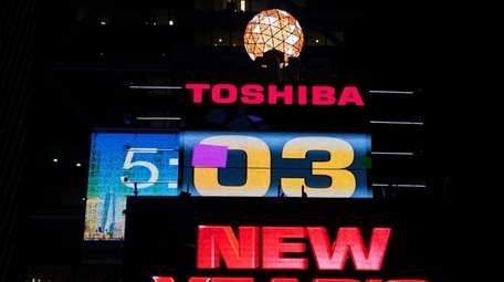 The Times Square Ball illuminates briefly above One