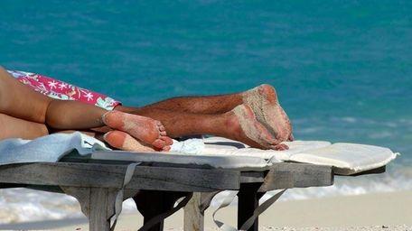 A couple sunbathes on a beach in Turks