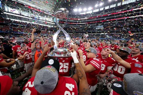 The Wisconsin Badgers celebrate with the trophy after