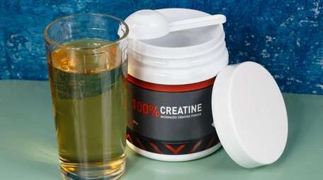 A creatine supplement alongside a glass of grape