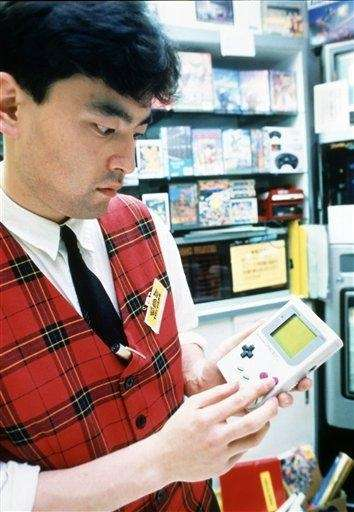 An unidentified Tokyo salesperson plays with a Nintendo