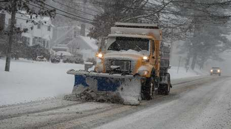 A Suffolk County DPW truck plows Motor Parkway