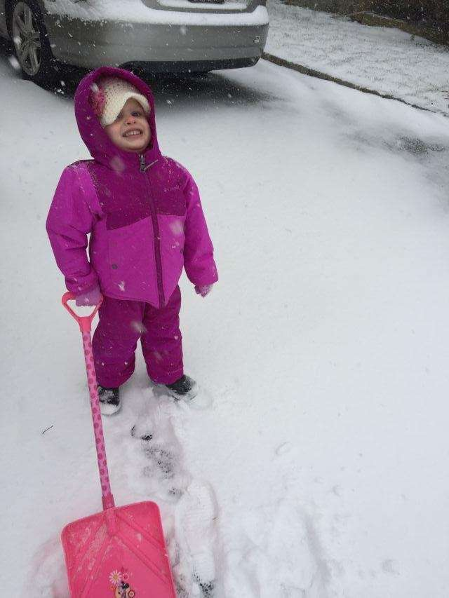 Izzy Skelly shoveling out the driveway
