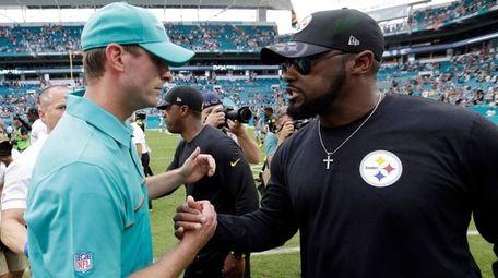 Miami Dolphins head coach Adam Gase, left, greets