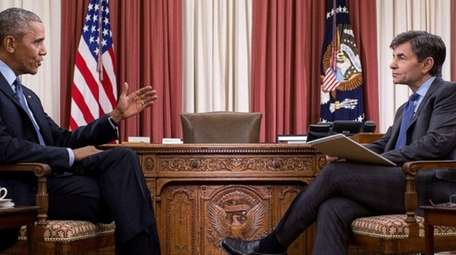 President Barack Obama sits with