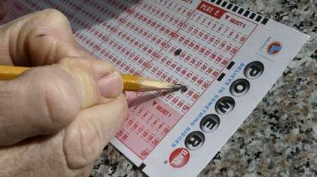 A lottery player fills out numbers on a