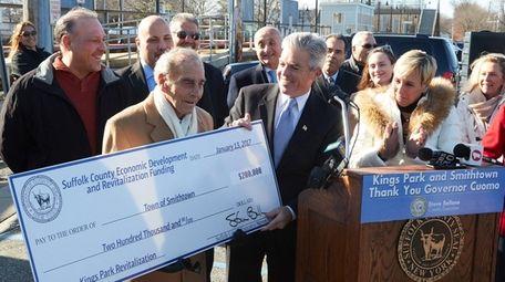 Suffolk County Executive Steve Bellone, right, presents Smithtown