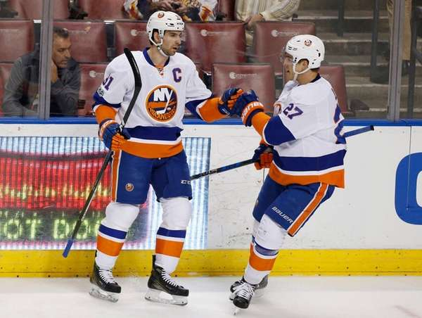 John Tavares, left, is congratulated by Anders Lee