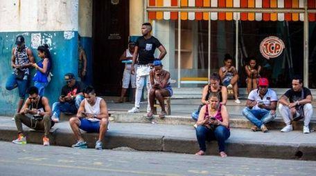 People outside a public Wi-Fi hotspot in Havana,